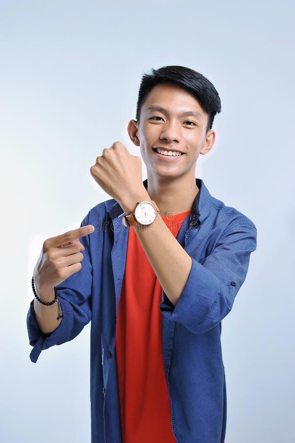 Potrait av den stiliga unga asiatiska mannen som pekar till armbandsuret med nätt le royaltyfri foto