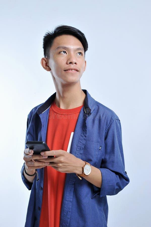 Potrait av den stiliga unga asiatiska mannen som rymmer en smart telefon och att bära armbandsuret med nätt le blick på kopiering royaltyfri bild