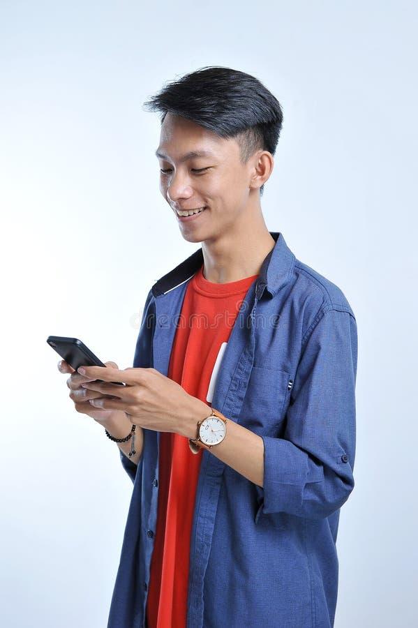 Potrait av den stiliga unga asiatiska mannen som rymmer en smart telefon och att bära armbandsuret med nätt le blick på telefonen arkivbilder