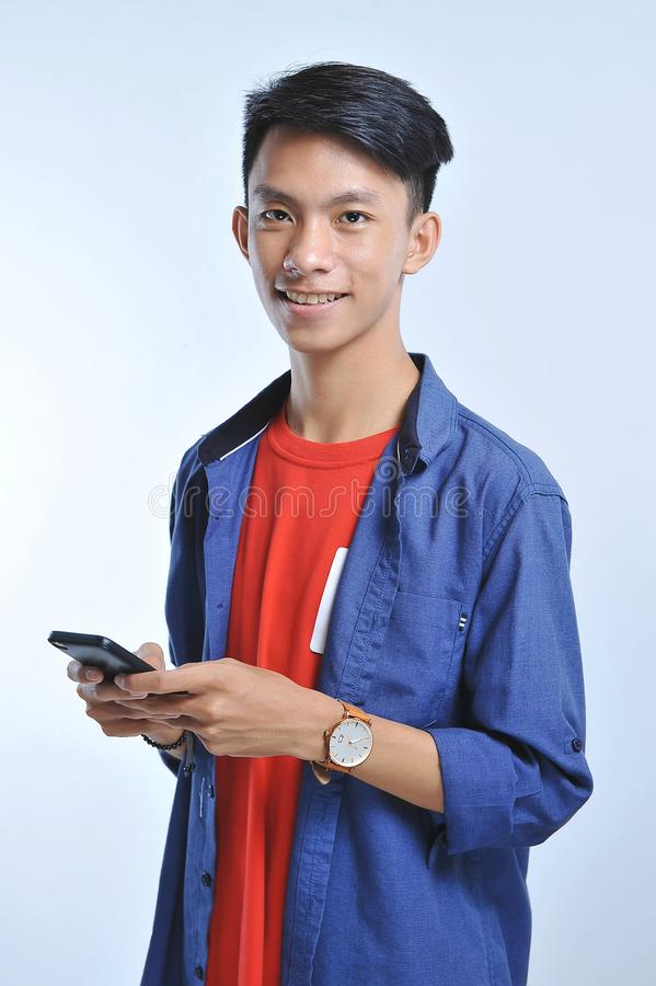 Potrait av den stiliga unga asiatiska mannen som rymmer en smart telefon och att bära armbandsuret med nätt le blick på kameran royaltyfria foton