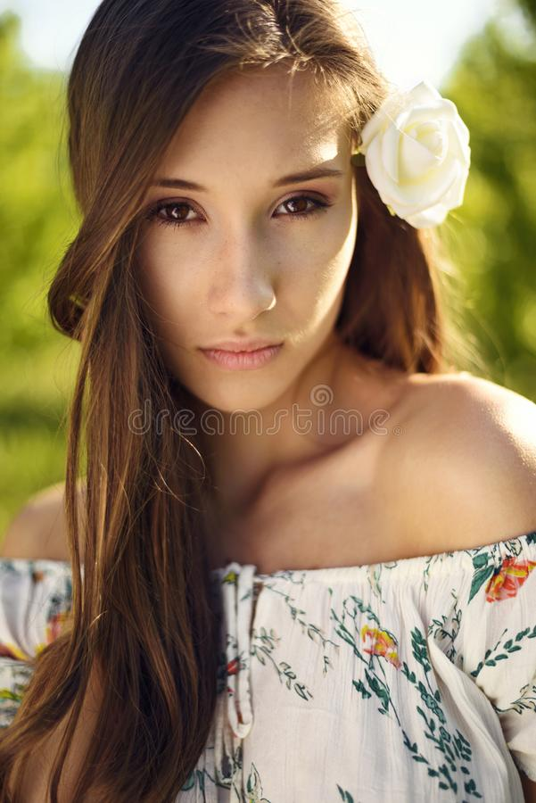 Potrait beautyy женщины с белой розой в ее волосах с солнечным светом светя вниз на ей стоковое фото