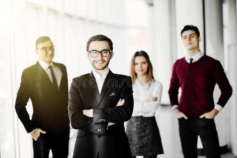 Potrait d'un homme d'affaires se tenant devant l'équipe d'affaires dans le hall de bureau photographie stock