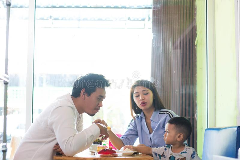 Potrait der asiatischen Familie sitzend innerhalb eines Caf?s, das ein Kuchengenie?en isst und spielt stockbild