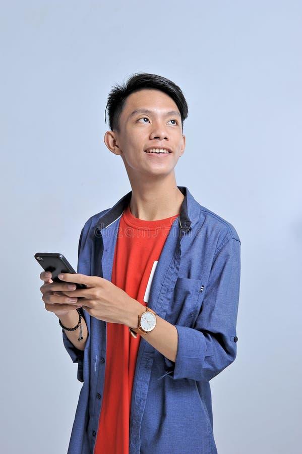Potrait van de knappe jonge Aziatische mens die een smartphone en slijtagepolshorloge met vrij het glimlachen houden bekijkt de e stock foto
