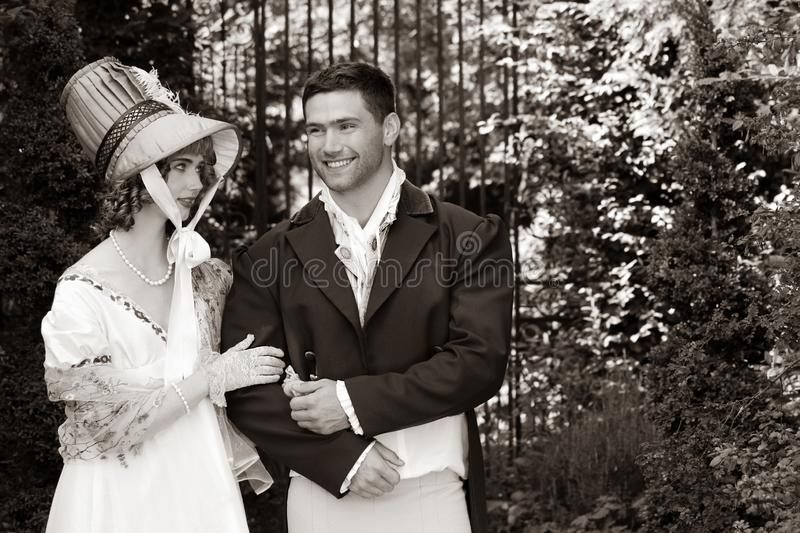 Potrait of young attractive couple dressed in vintage clothing walking through garden arm in arm, smiling royalty free stock images