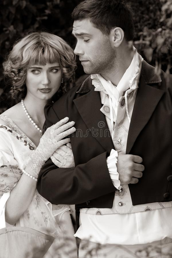 Potrait of young attractive couple or lovers in period costume standing in garden arm in arm as female looks thoughtful stock photos
