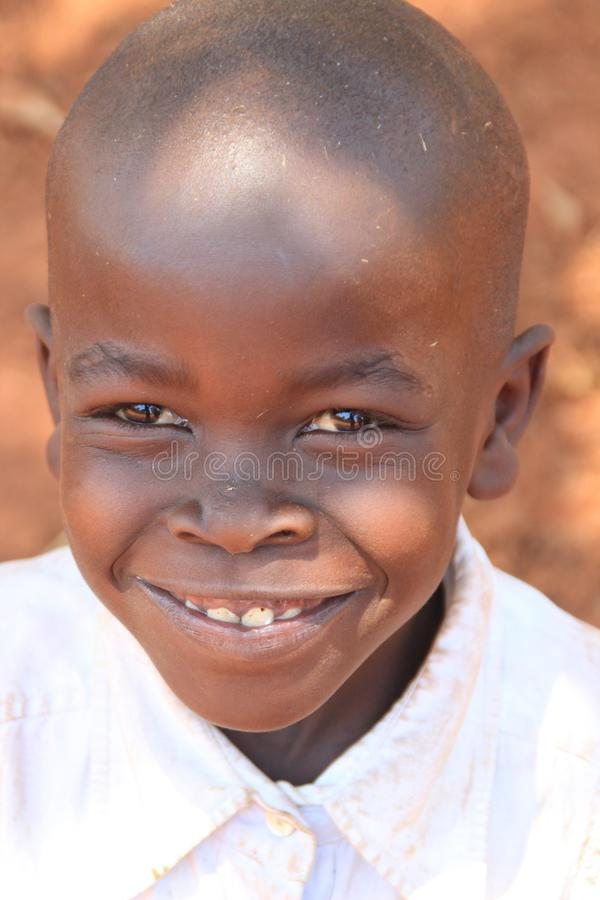 Potraite del muchacho africano del pueblo que sonríe y jugar cerca de hogar en el suburbio de Kampala fotografía de archivo