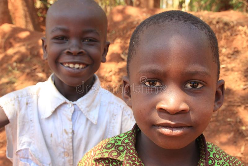 Potraite del muchacho africano del pueblo que sonr?e y jugar cerca de hogar en el suburbio de Kampala imagen de archivo