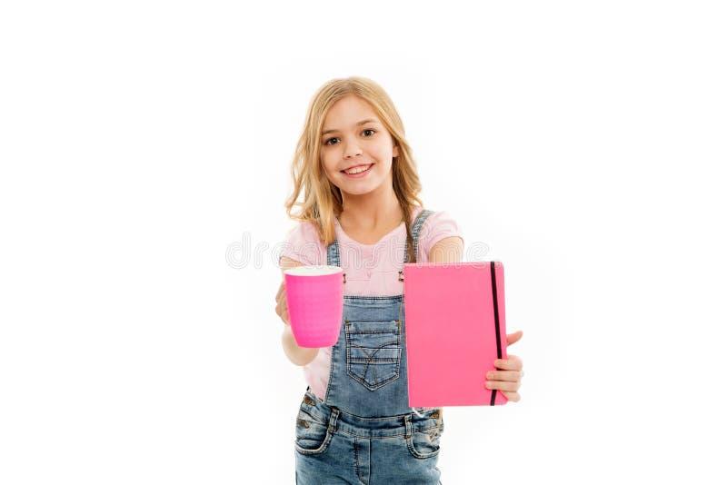 Potrzebuje zwiększenie Ślicznej dziewczyny trzyma herbacianą filiżankę i nutową książkę Mały dzieciak cieszy się jej ranek herbat fotografia stock
