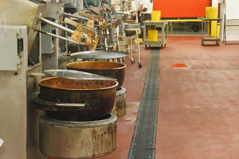 Pots in a Chocolate Factory. Empty copper pots at assembly line in a chocolate factory stock photo