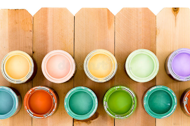 Pots of colorful wood stain on a fence. Opened pots of colorful wood stain arranged as a lower border on a natural wooden picket fence, offering a choice of stock image