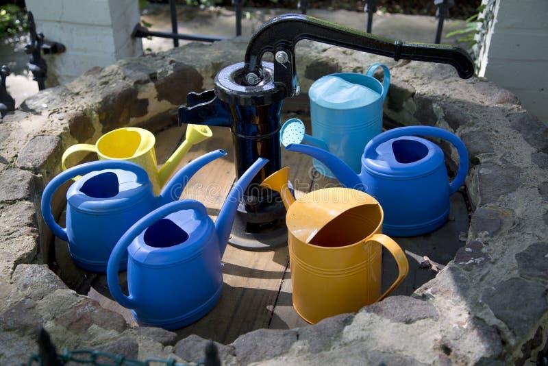 Pots d'arrosage colorés autour de puits de pompage image stock