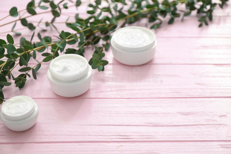 Pots d'hydrater la crème avec l'extrait de fines herbes sur la table en bois image libre de droits