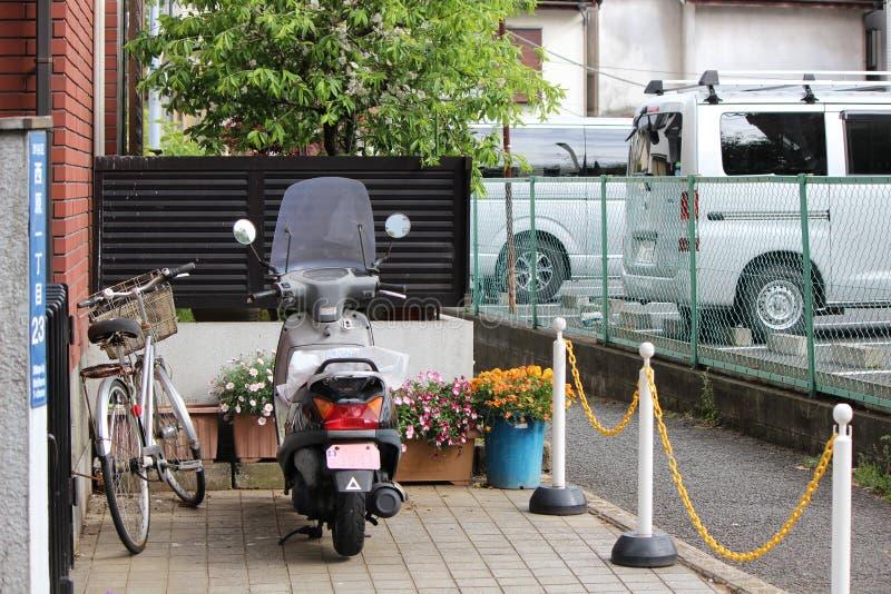 Pots de bicyclette, de scooter et de fleur devant le bâtiment résidentiel photo stock