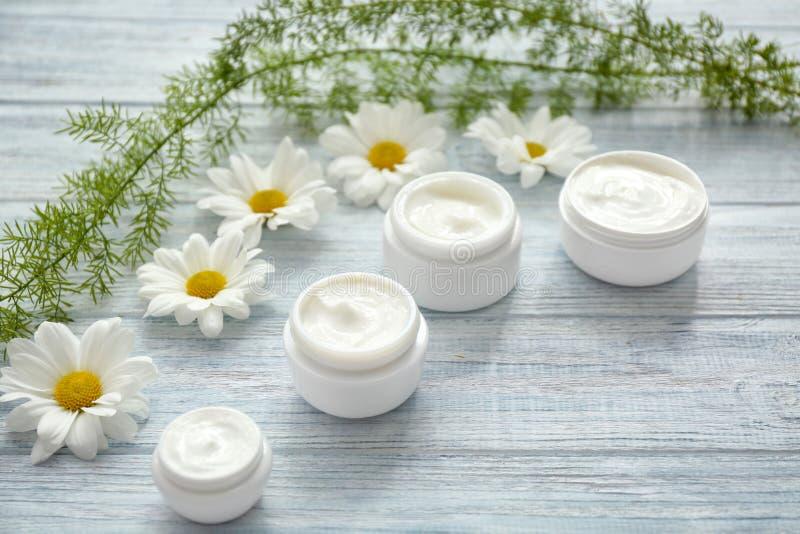 Pots de crème avec l'extrait de fines herbes sur le fond en bois blanc photographie stock