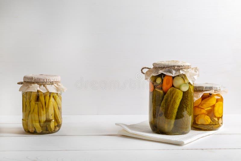 Pots de légumes marinés : concombres, tomates, aubergines sur le fond en bois rustique images libres de droits