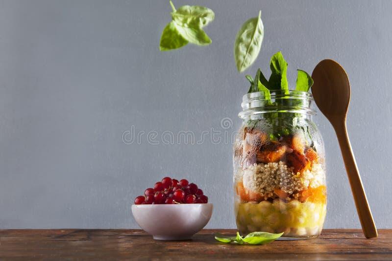Pots de maçon avec de la salade chaude : Les pois chiches, arrots, quinoa, ont rôti l'unité centrale photographie stock