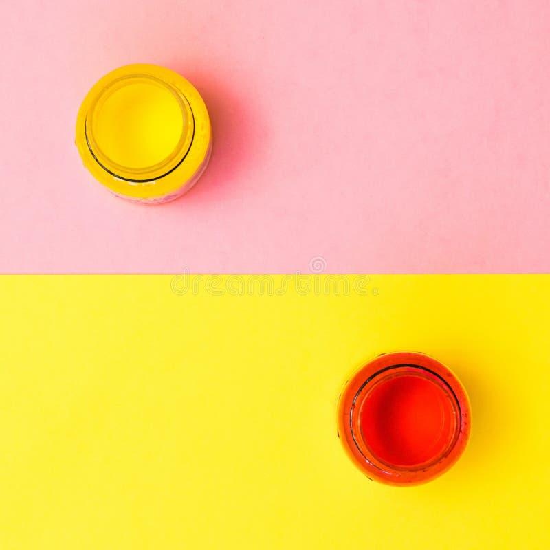 Pots de peinture rouge et jaune sur un jaune et un fond rose Kit cr?atif photo stock
