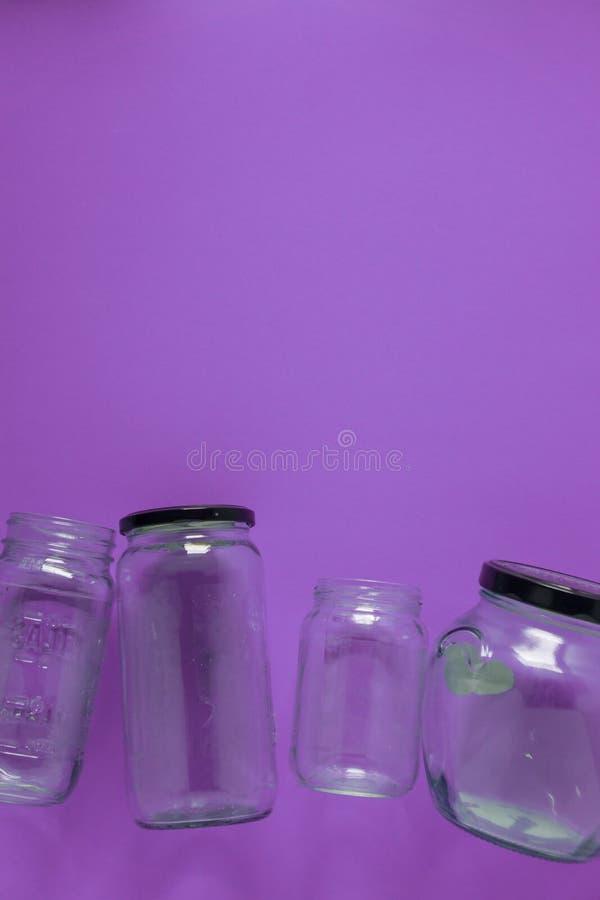 Pots en verre d'isolement, à plat sur le fond pourpre violet, pièce pour le dessus de l'espace de copie image stock