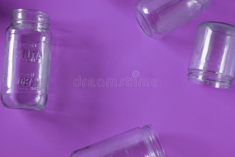 Pots en verre d'isolement, aucun couvercles à plat, fond pourpre violet, pièce de l'espace de copie images stock