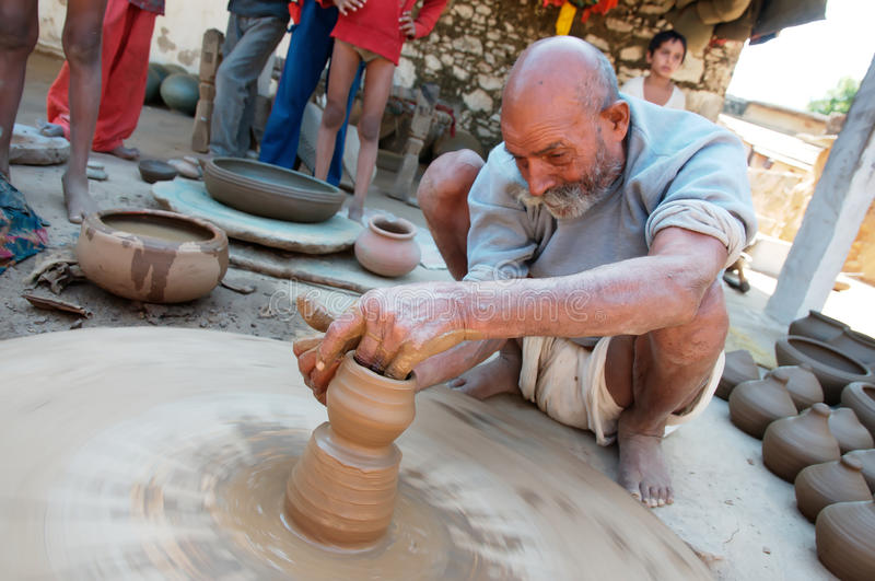 Pots factory worker. An old indian man is setting up a crock pot using a rudimental lathe