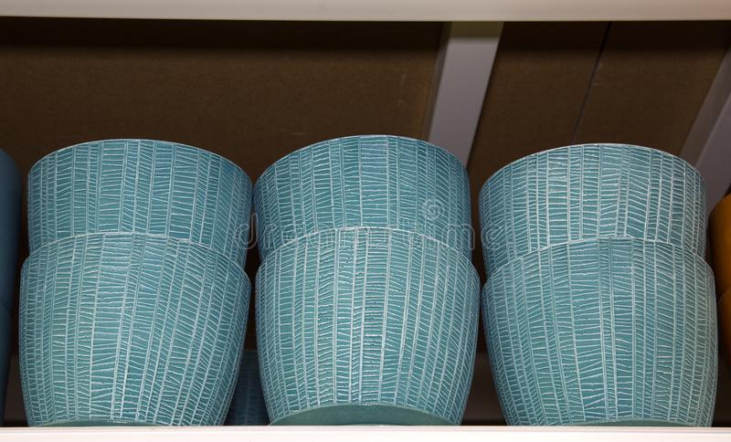 Pots for flowers of blue color with a beautiful white pattern in a grid. Crop production stock photos