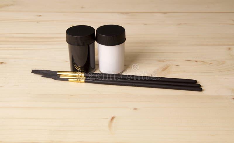 Pots noirs et blancs de peinture avec des brosses photographie stock libre de droits
