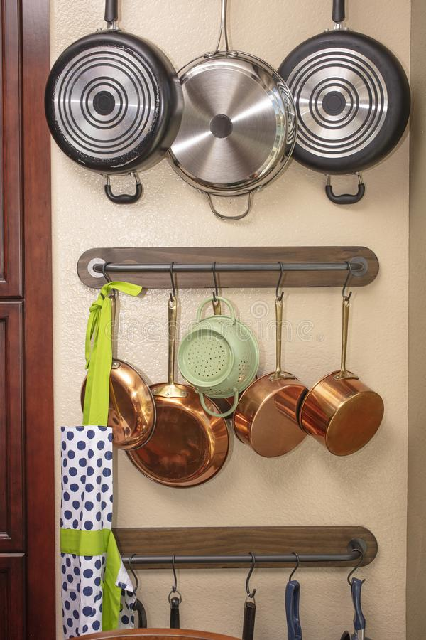 Pots and pans hanging on a kitchen wall to save space. Pots and pans hanging on a kitchen wall and hooks to save space royalty free stock image