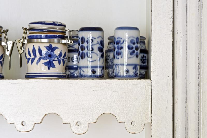 Pots of spices in blue porcelain, on white cabinet shelf stock photography
