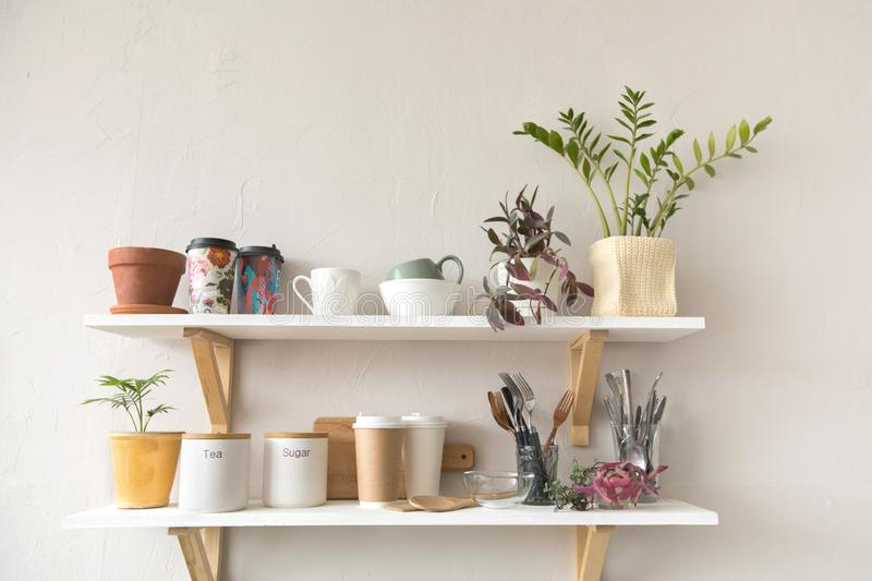 Utensils and mugs on shelf. Pots with various houseplants and assorted dishware standing on shelf in cozy kitchen royalty free stock image