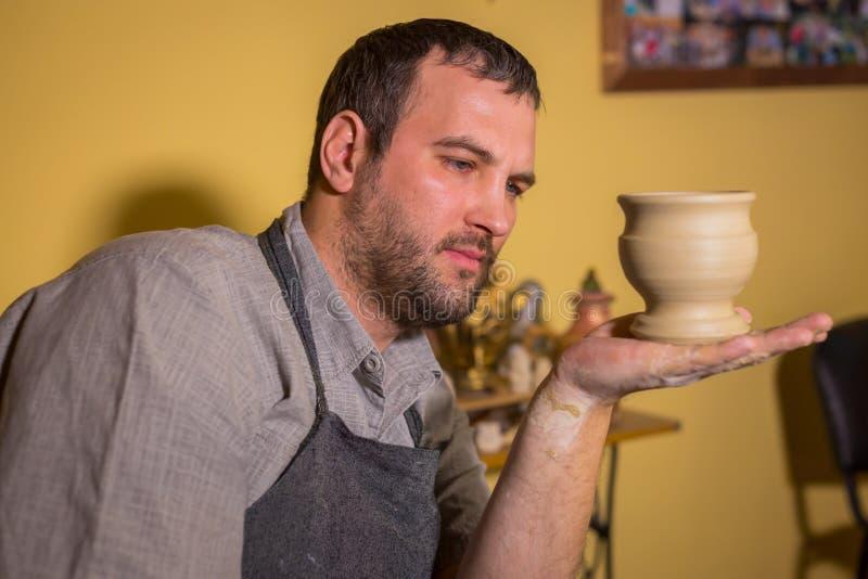 Pottenbakker die aardewerkmok onderzoeken stock foto