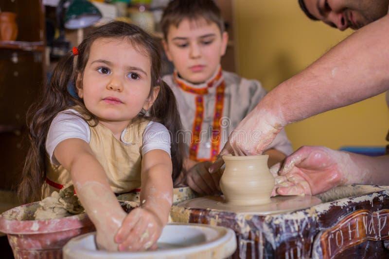 Pottenbakker die tonen hoe te met ceramisch in aardewerkstudio te werken stock afbeelding