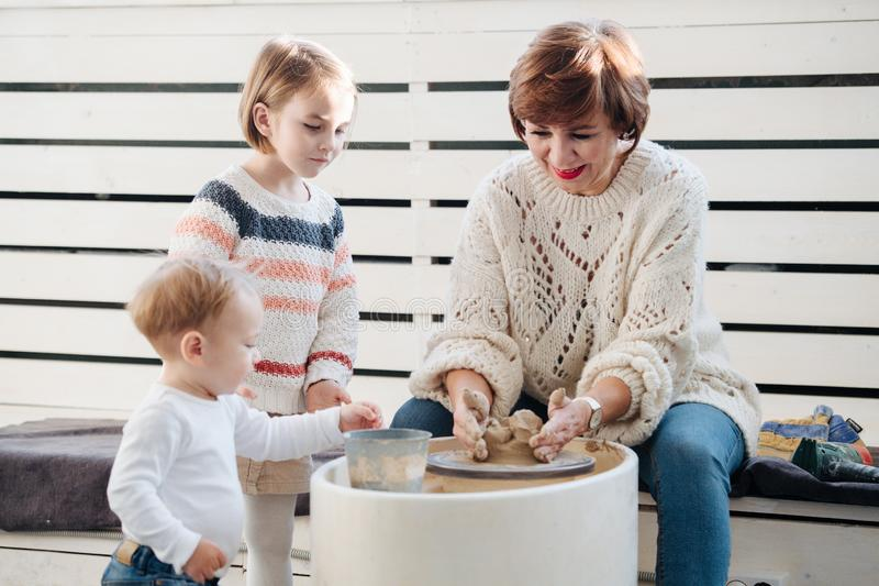 A potter craftsman shows a small girl how to work with clay and pottery wheel. Brother watching. stock images