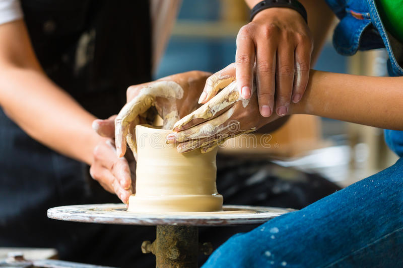 Potter creating clay bowl on turning wheel. Female Potter creating a bowl on a Potters wheel, the master potter helping her stock photo