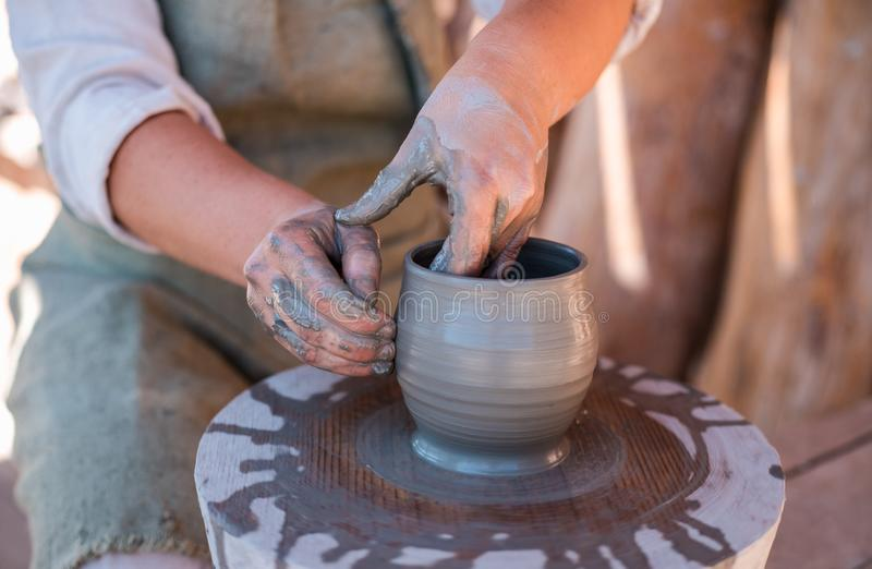 Potter is creating earthenware on potter`s wheel. Potter`s hands are creating earthenware on potter`s wheel. Concept of natural materials, hand made and royalty free stock photography