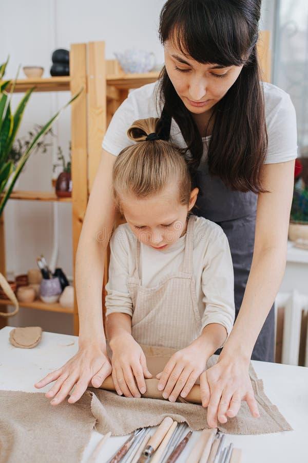 Potter ensina garotinho a rolar barro Em um workshop fotos de stock royalty free