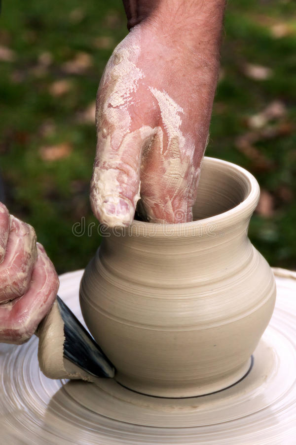 Potter hands pot. Potter hands working with clay making a pot which is placed on potter`s wheel