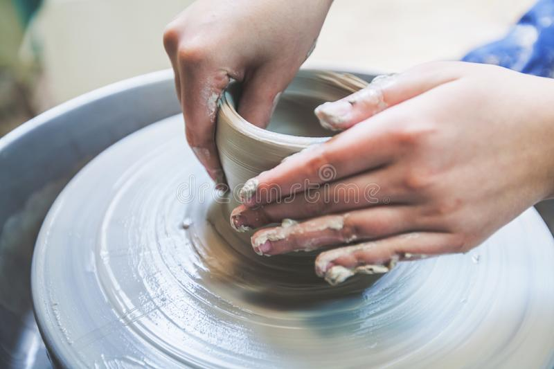 Potter hands working with clay on pottery wheel. Potter at work shaping clay on pottery wheel at workshop stock images