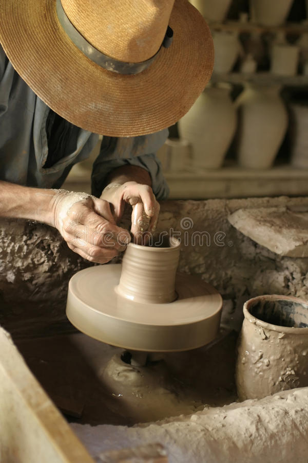 Potter at his wheel. Potter throwing a cup on an old kick pottery wheel stock images