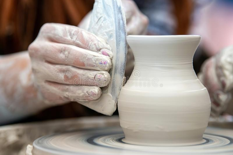 Potter makes pottery dishes on potter`s wheel. Hands of the potter. The potter makes pottery dishes on potter`s wheel. The sculptor in workshop makes clay stock images