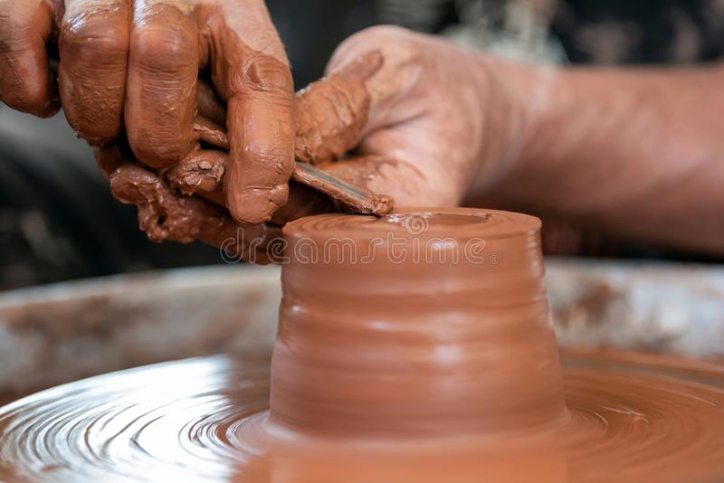 Potter makes pottery dishes on potter`s wheel. Hands of the potter. The potter makes pottery dishes on potter`s wheel. The sculptor in workshop makes clay royalty free stock images