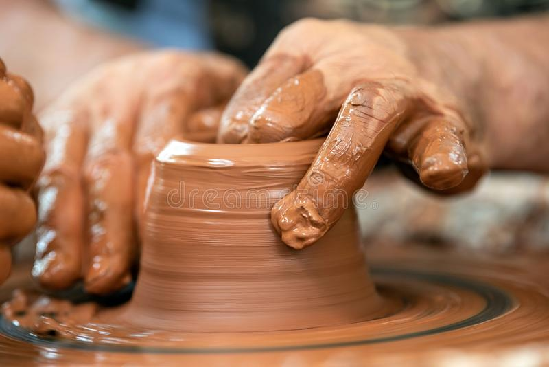 Potter makes pottery dishes on potter`s wheel. Hands of the potter. The potter makes pottery dishes on potter`s wheel. The sculptor in workshop makes clay stock photography