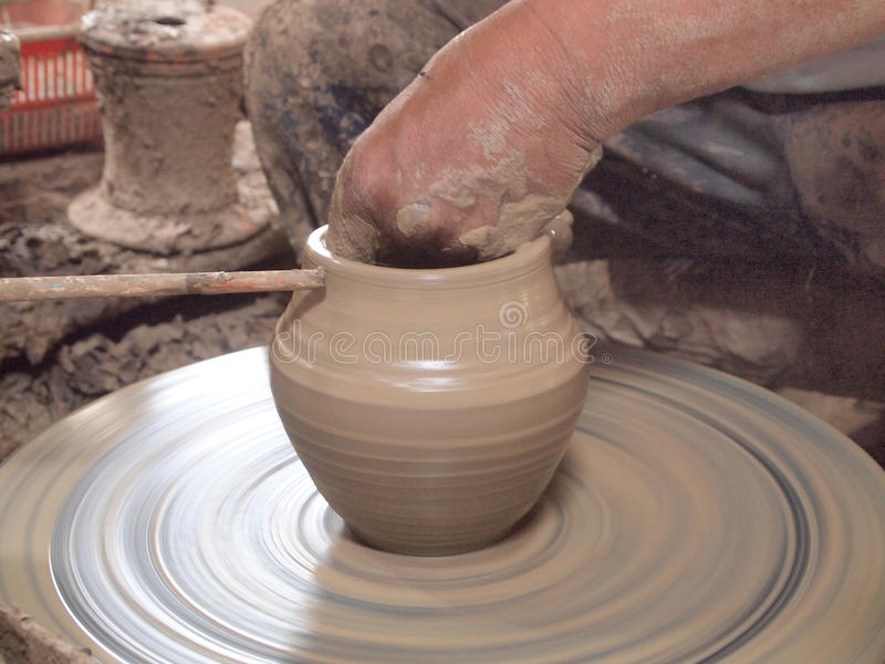 Potter makes on the pottery wheel clay pot. The hands of a potter with the tool. Close-up stock image