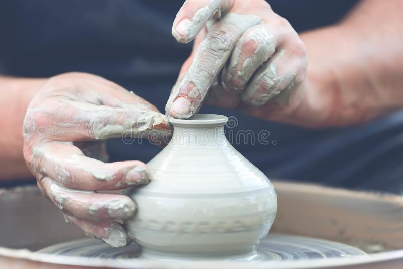 Potter making ceramic pot on the pottery wheel. Hands of a potter. Potter making ceramic pot on the pottery wheel stock image