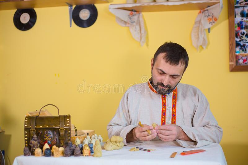 Potter making clay figure for board game. Professional male potter in russian ethnic shirt making clay figure for medieval popular strategy board game - tafl royalty free stock image