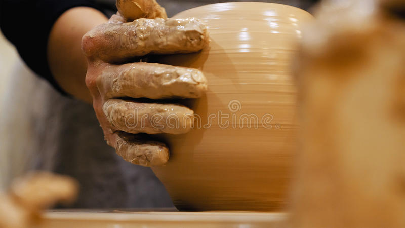 Potter is making clay pot on the potter`s wheel. Potter is making clay pot bowl or vase ceramics porcelain on the potter`s wheel. Creating pottery art and stock images