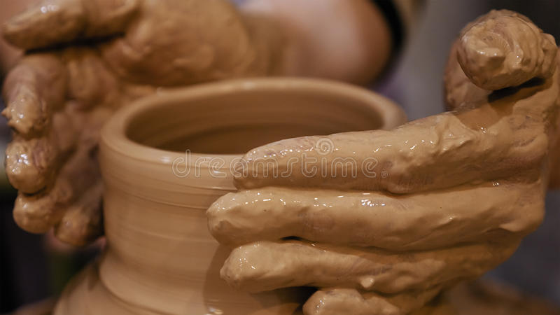 Potter is making clay pot on the potter`s wheel. Potter is making clay pot bowl or vase ceramics porcelain on the potter`s wheel. Creating pottery art and stock image