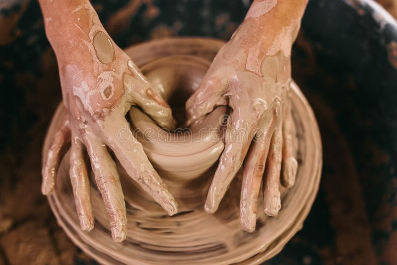 Potter moulding clay on pottery wheel. Potter making a clay pot on pottery wheel in workshop. Close up of hands of craftswoman moulding clay on pottery wheel royalty free stock image