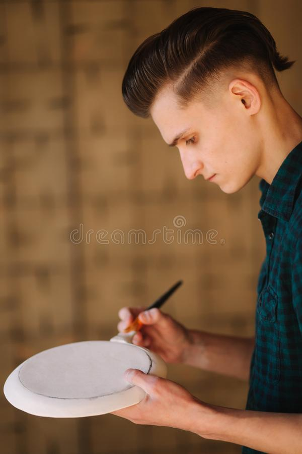 Potter making ornament on ceramic plate. Professional male potter draw a pencil on ceramic product royalty free stock photography
