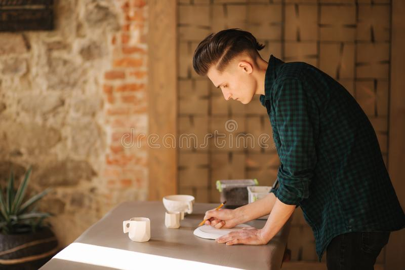 Potter making ornament on ceramic plate. Professional male potter draw a pencil on ceramic product stock photography